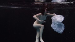 Redhead beauty swims underwater in a white dress Thumb