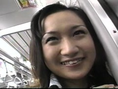 Young asian girl on a train full of people Thumb